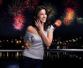 Beautiful brunette on a fireworks background — Stockfoto