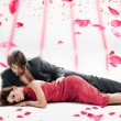 Attractive couple over falling rose petals — Stock Photo