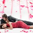 aantrekkelijke paar over dalende rozenblaadjes — Stockfoto