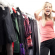 Young happy woman has a plenty of clothes to choose from - 