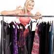 Stock Photo: Young happy womhas plenty of clothes to choose from