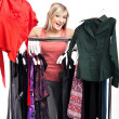 Young happy woman has a plenty of clothes to choose from - Stok fotoğraf