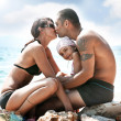 Young family embracing on a sandy beach — Stock Photo