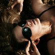 Beautiful young sexy blonde wearing sunglasses, laying in water — Stock Photo
