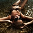 Beautiful young sexy blonde wearing sunglasses, laying in water — Стоковая фотография