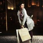 Joyful lady holding shopping bags, on the night — Stock Photo