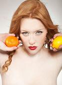 Young woman holding orange an lemon — Stock Photo