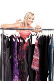 Young happy woman has a plenty of clothes to choose from — Stock Photo