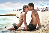 Happy couple kissing on seashore — Stock Photo
