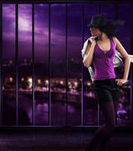 Dancing girl wearing a hat over abstract background — Stok fotoğraf