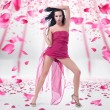 Young woman posing over rose petals background — Stock Photo #4532604