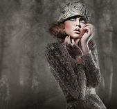 Beautiful young lady in a mysterious gray forest — Stock Photo