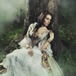 Young lady in a mysterious forest - Foto Stock