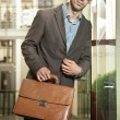 Confident young businessman holding a briefcase — Stock Photo