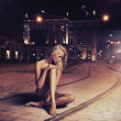 Naked young woman in sensual pose on the street — Stock Photo