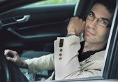 Handsome man sitting in a car — Stock Photo