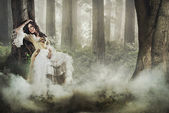 Gorgeous brunette beauty in a old-fashioned dress in a forest — Stock Photo