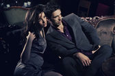Handsome couple sitting on sofa — Stock fotografie