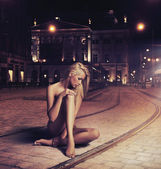 Naked young woman in sensual pose on the street — Foto de Stock