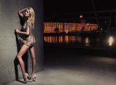 Sexy young blonde beauty posing over night city background — Stock Photo