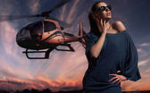 Fashionable lady wearing sunglasses with helicopter in the background — Stock Photo