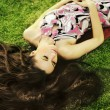 Young beauty brunette laying on the grass — Stock Photo #4580267
