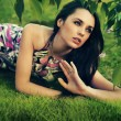 Young beauty brunette laying on the grass — Stock Photo