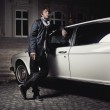 Handsome young man standing next to a limousine — Stock Photo