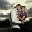 Beautiful couple hugging over cloudy sunset - Lizenzfreies Foto