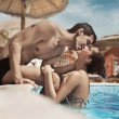 Young couple kissing in a swimming pool - Stock Photo