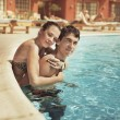 Foto Stock: Young couple kissing in a swimming pool