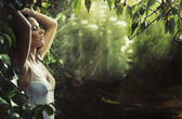 Adorable sexy brunette in a rain forest — Stock Photo