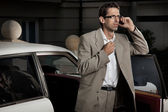 Young man speaking the phone next to the car — Stock Photo