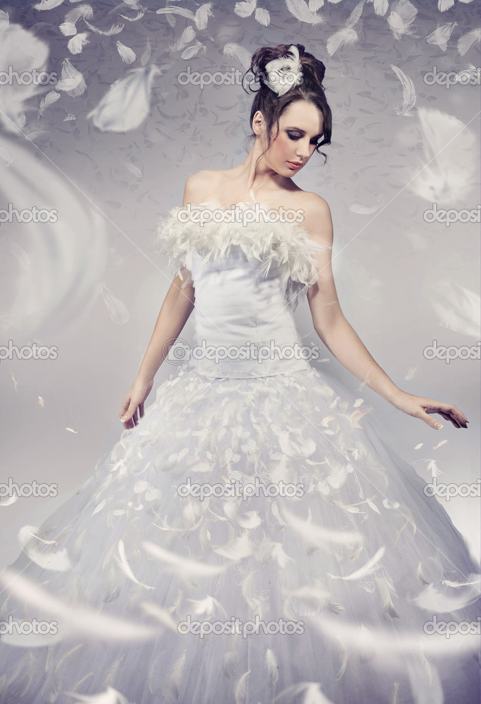 Beautiful bride posing over white flying feathers  — Stock Photo #4581345