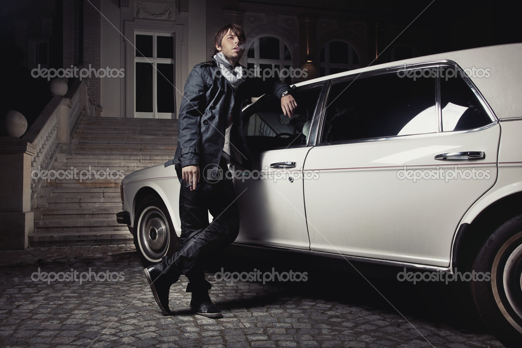 Handsome young man standing next to a limousine   Stock Photo #4581433