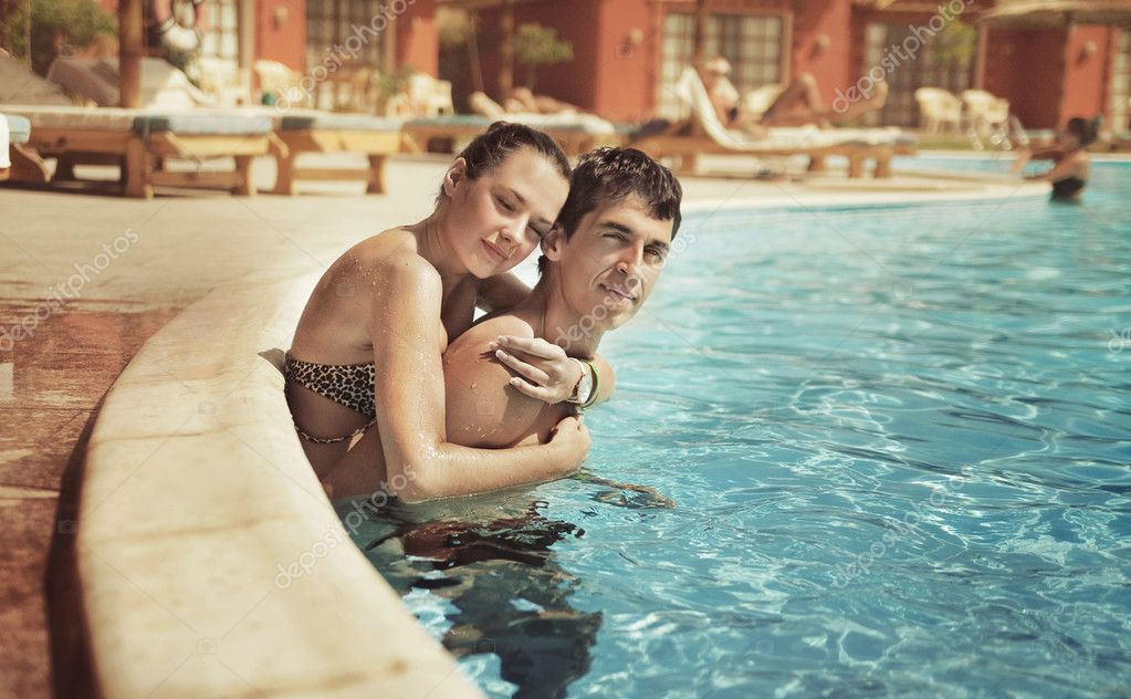 Young couple kissing in a swimming pool   Stock Photo #4585051