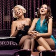 Two pretty girls watching something, smiling and drinking wine - 