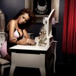 Pretty young woman sitting and preparing for the event — Stock Photo
