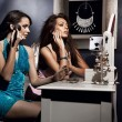 Two beautiful girls doing make up befor night party - Lizenzfreies Foto
