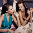 Two smiling women doing make up - 