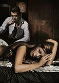 Sexy jovem mulher deitada sobre o mau e homem bebendo vinho — Foto Stock