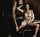 Yatakta oturmuş şaşırtıcı genç seksi esmer — Stok fotoğraf