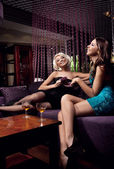Pretty young girls talking and drinking on the party — Stock Photo