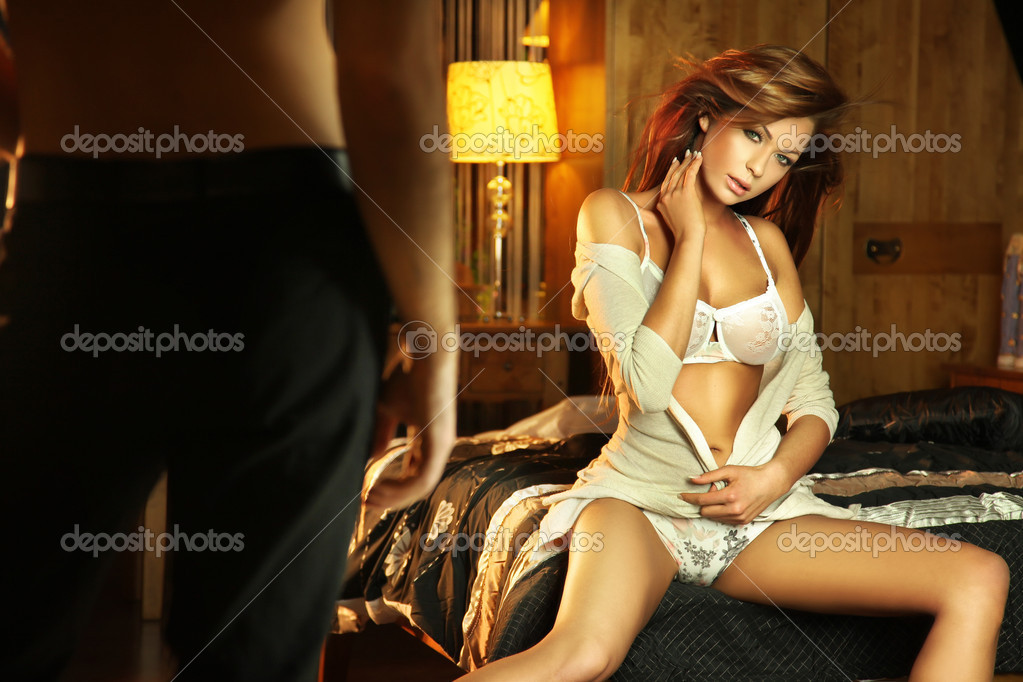 Cute brunette in lingerine sitting on the bed and waiting for a man — Stock Photo #4750381
