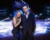 Mladý pár nad noční město pozadí — Stock fotografie