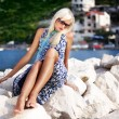 Pretty blonde woman relaxing near the water - Stock Photo