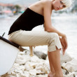 Beautiful blonde girl sitting at the lake - Stok fotoraf