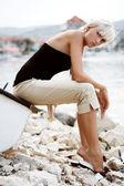 Beautiful blonde girl sitting at the lake — Stock Photo