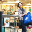 Cute brunette girl smiling on shopping - Zdjęcie stockowe