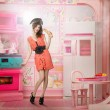 Young woman like a doll cokking in pink kitchen — Stock Photo #5060539